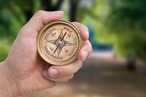 Hand Holding Christian Compass